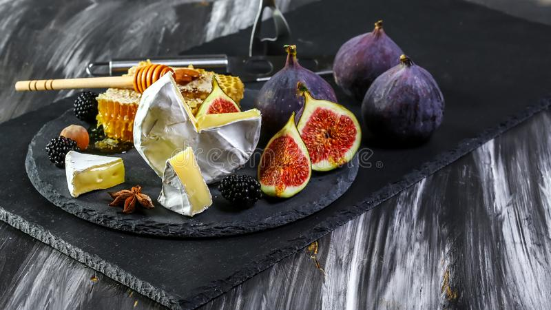 乳酪板、软制乳酪用无花果和蜂蜜 乳酪板、软制乳酪用无花果和蜂蜜和白酒 r 免版税库存照片