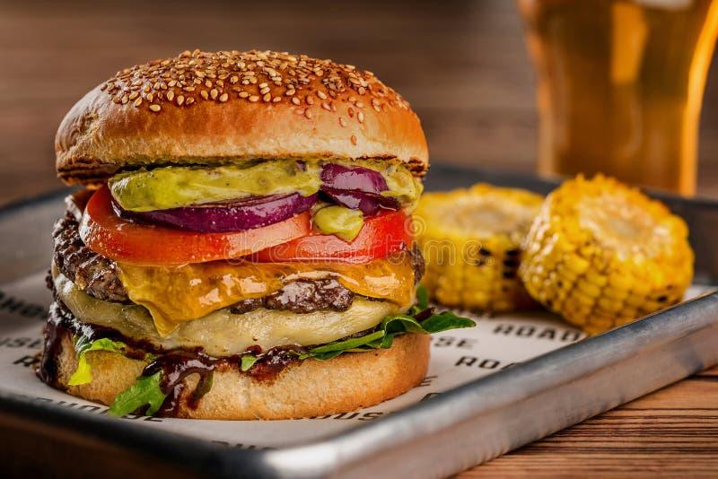 乳酪汉堡,做由与蕃茄切片的黑麦小圆面包和熔化乳酪在烤牛肉和莴苣叶子在木 库存图片