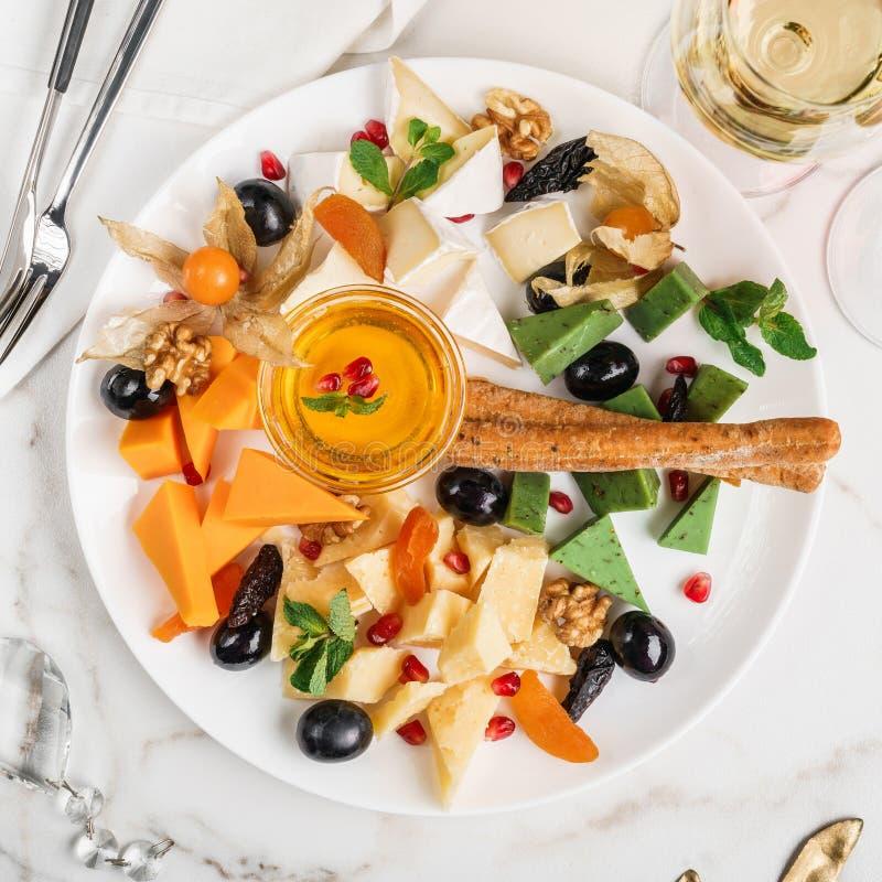 乳酪盘子、绿色乳酪、咸味干乳酪乳酪供食用酒,面包条和蜂蜜在轻的大理石背景 快餐和酒 库存图片