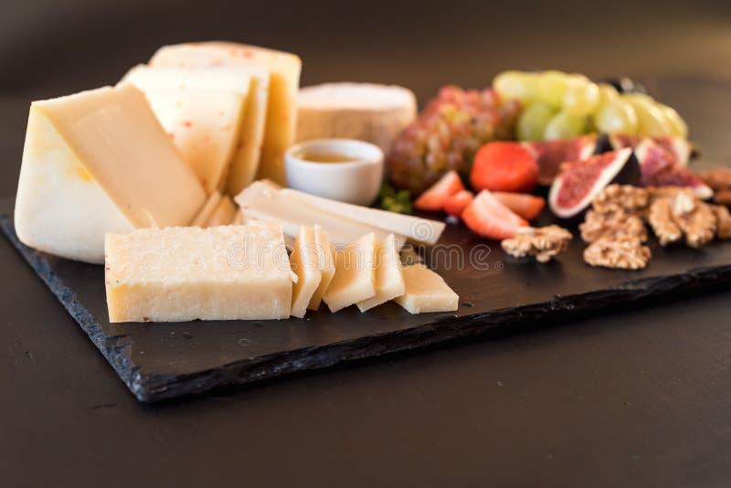 乳酪盘子以开胃菜品种在桌上的 免版税库存照片