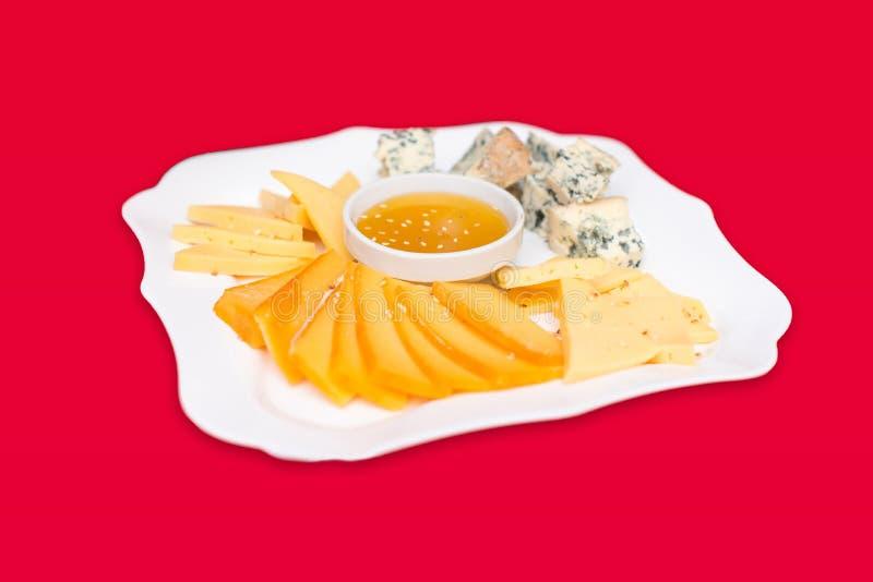 乳酪盘子用蜂蜜、Dor蓝色、巴马干酪、Bree、软制乳酪和羊乳干酪在一个桌设置与一张红色桌布 图库摄影
