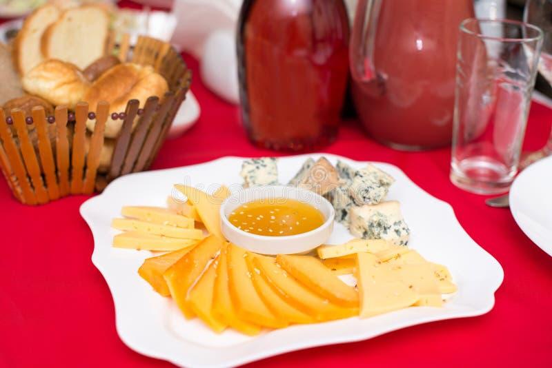 乳酪盘子用蜂蜜、Dor蓝色、巴马干酪、Bree、软制乳酪和羊乳干酪在一个桌设置与一张红色桌布 库存照片