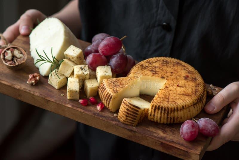 乳酪盛肉盘在手上 免版税库存照片