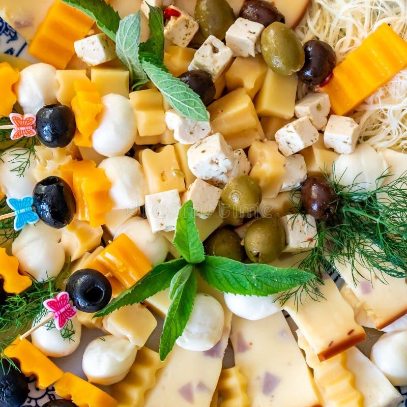 乳酪盛肉盘,分类用橄榄和绿叶在板材 库存照片