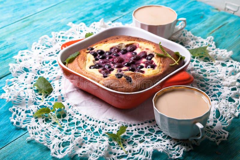 乳酪蛋糕用莓果用咖啡,烘烤,蓝色背景 库存照片