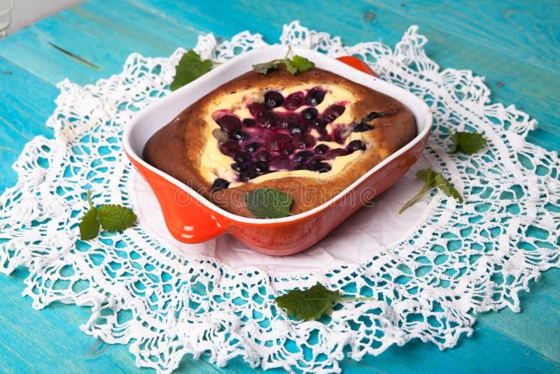 乳酪蛋糕用莓果,烘烤,蓝色背景 免版税库存照片