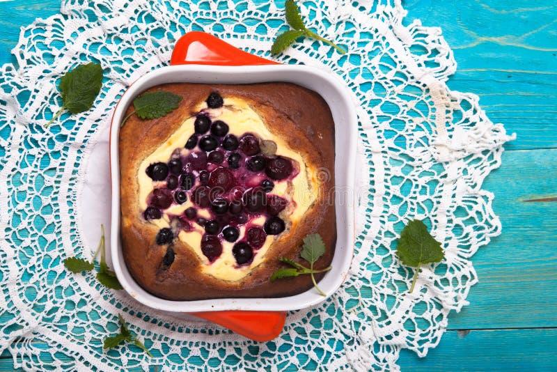 乳酪蛋糕用莓果,烘烤,蓝色背景 库存图片