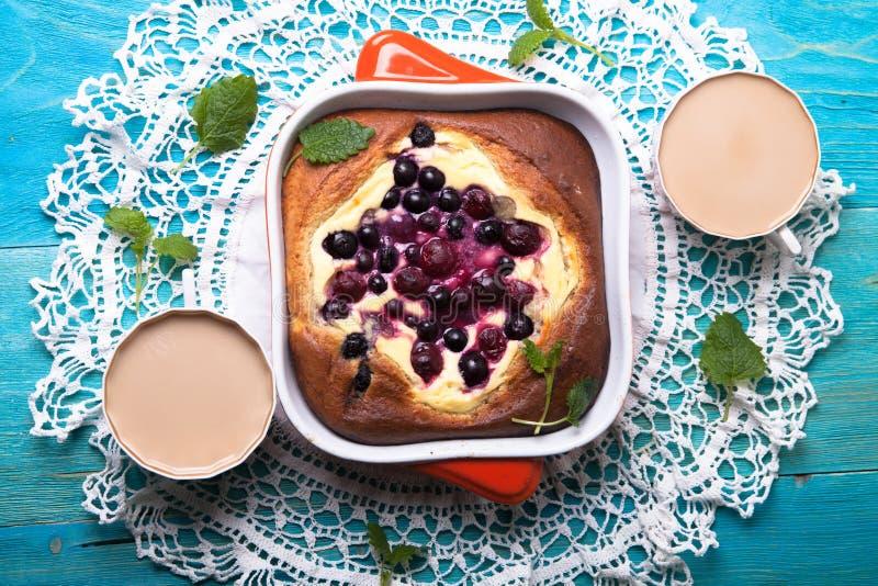 乳酪蛋糕用莓果,烘烤,蓝色背景 图库摄影