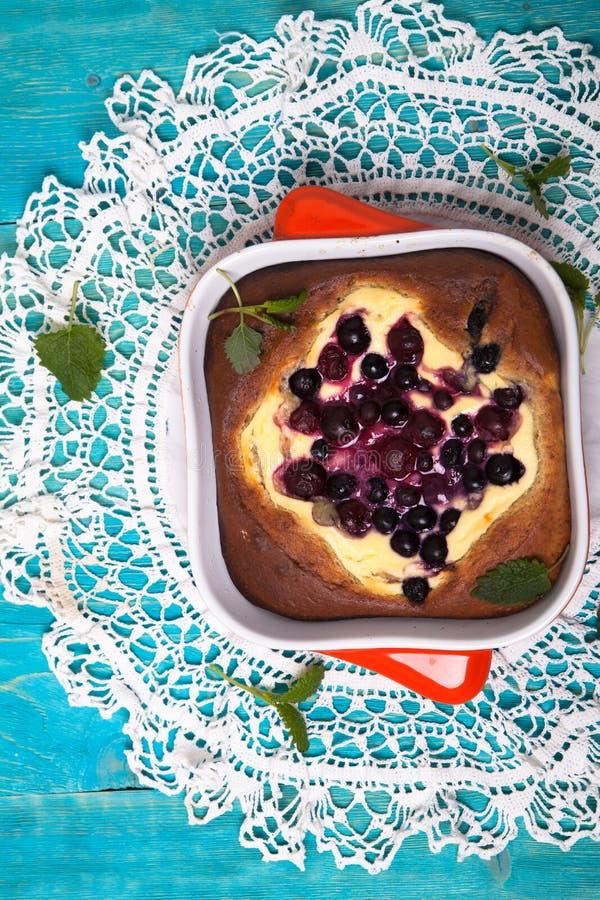 乳酪蛋糕用莓果,烘烤,蓝色背景 免版税库存图片