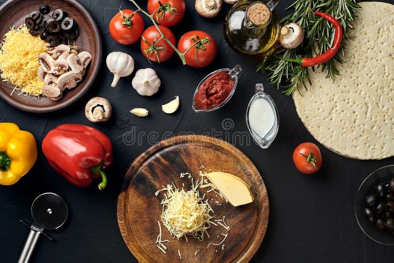 乳酪,在黑桌上的不同的菜 传统意大利薄饼的成份 免版税库存照片
