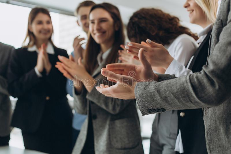 了不起的工作!成功的企业队在现代工作站拍他们的手,庆祝新产品表现  库存图片
