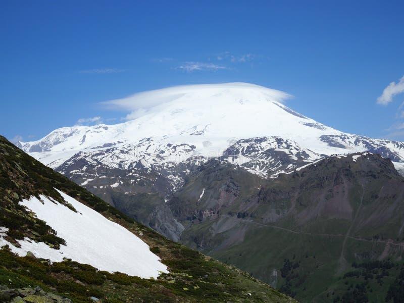 了不起的自然山脉 白种人雪山或火山有绿色领域的厄尔布鲁士山,天空蔚蓝令人惊讶的透视  库存照片
