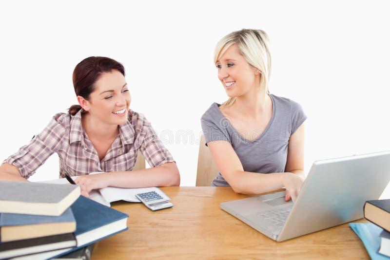 了解与膝上型计算机和书的可爱的妇女 免版税库存照片