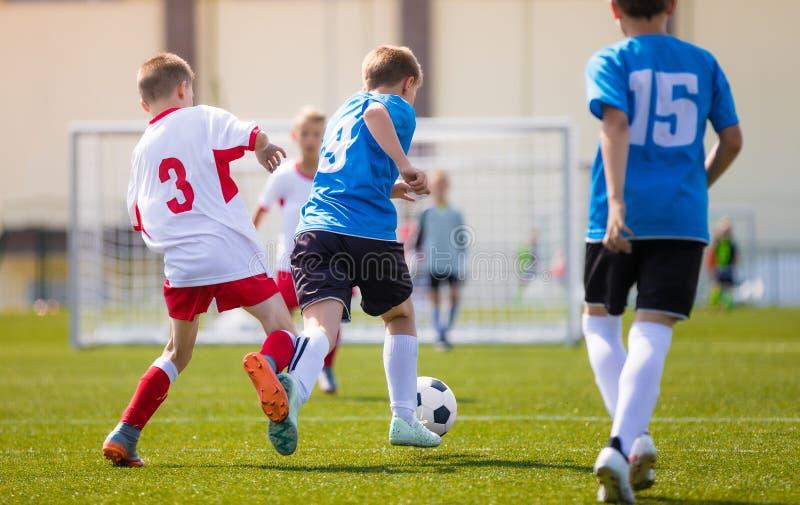 争夺球的两个男孩足球队员在足球赛期间 免版税图库摄影