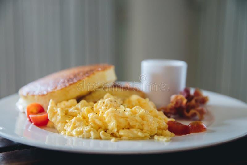 争夺鸡蛋用薄煎饼和烟肉在影片葡萄酒样式的早餐 图库摄影