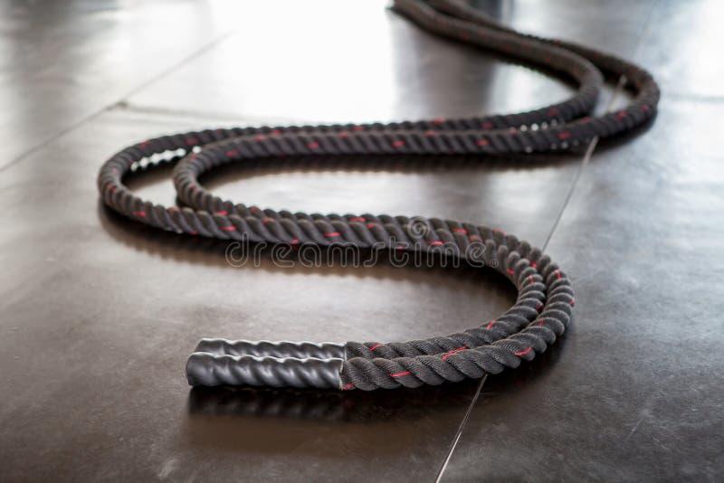 争斗绳索在健身健身房的黑地板上说谎 库存照片