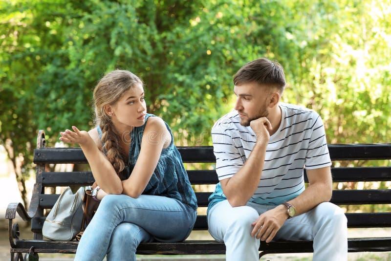 争论年轻的夫妇,当坐长凳在公园时 免版税库存图片