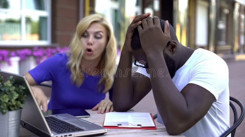 争论紧张的商人,看膝上型计算机和纸板,麻烦 图库摄影