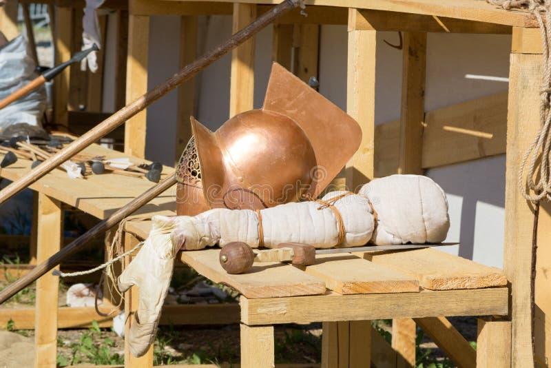 争论者盔甲、剑和矛在长木凳 库存照片