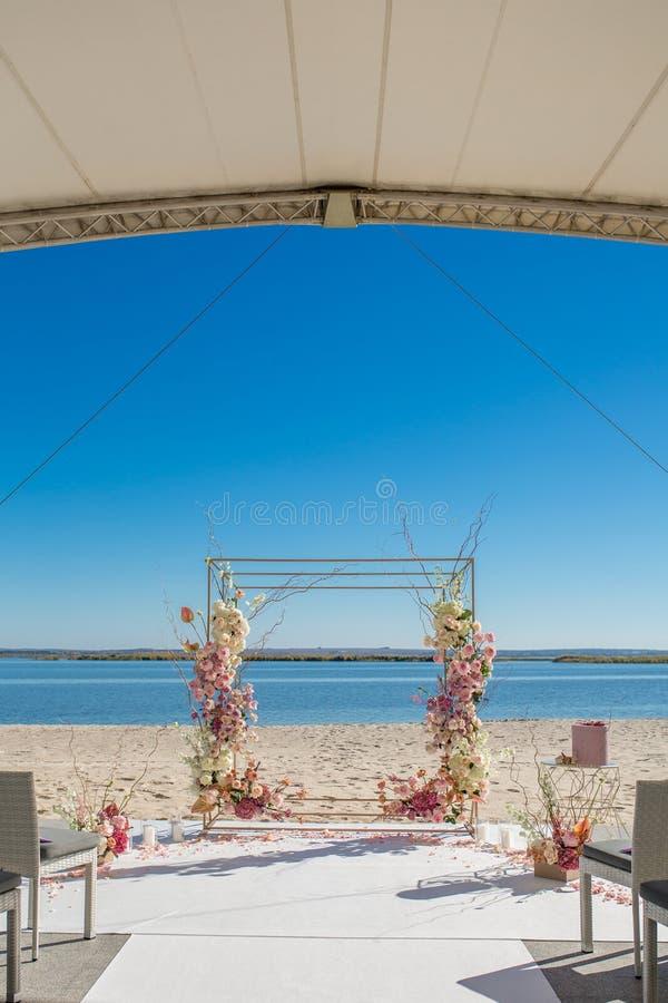 事件装饰 在河沿的婚姻的chuppa用鲜花装饰了 卖花人工作流 库存图片