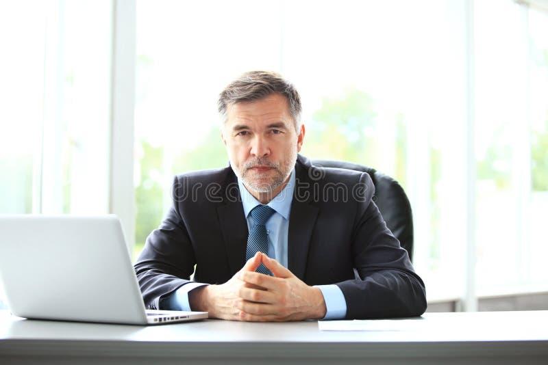事务、人们和技术概念-与便携式计算机办公室的愉快的微笑的商人 图库摄影