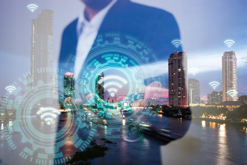 事务、技术和互联网连接概念两次曝光  使用象wifi在手边和现代城市的商人 图库摄影