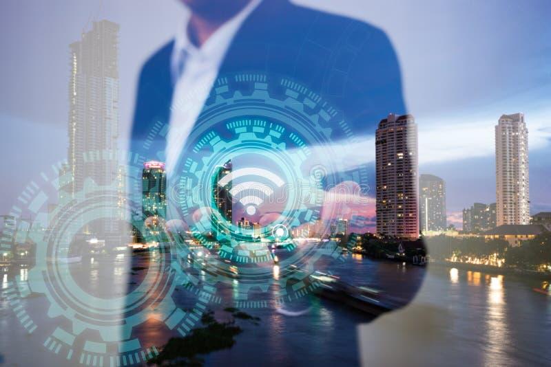 事务、技术和互联网连接概念两次曝光  使用象wifi在手边和现代城市的商人 免版税图库摄影