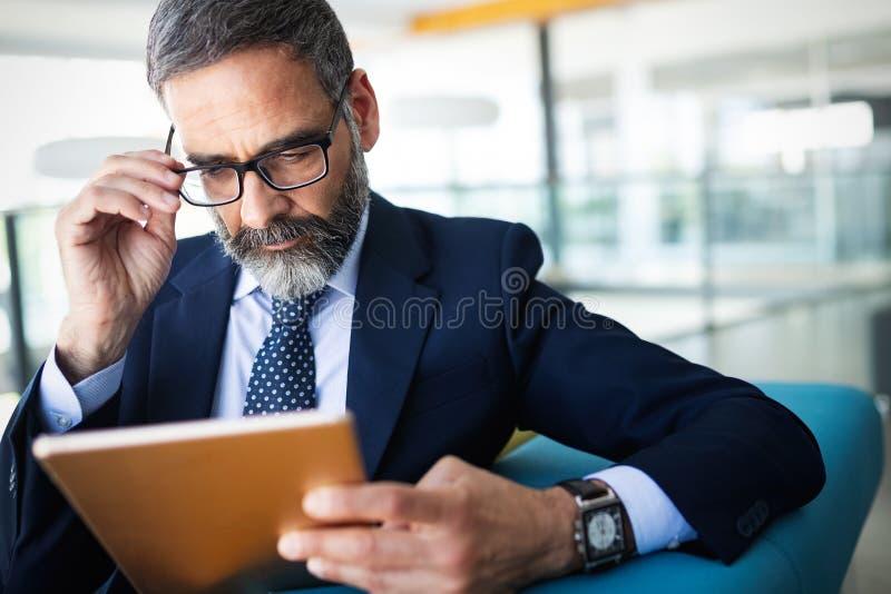 事务、技术和人概念-与运作在办公室的平板电脑的资深商人 库存照片