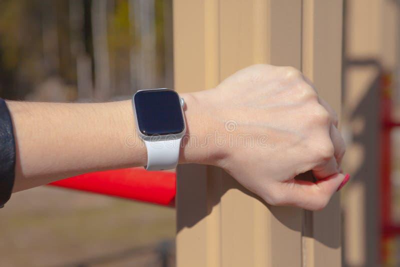 事务、技术和人概念-关闭设置巧妙的手表的妇女手 库存照片