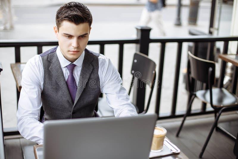 事务、技术和人概念-有一个膝上型计算机和咖啡杯的年轻人在城市街道咖啡馆 免版税库存图片