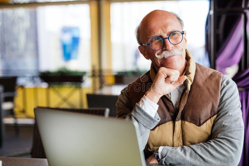 事务、技术和人概念-有便携式计算机的老人在城市街道咖啡馆 免版税库存照片