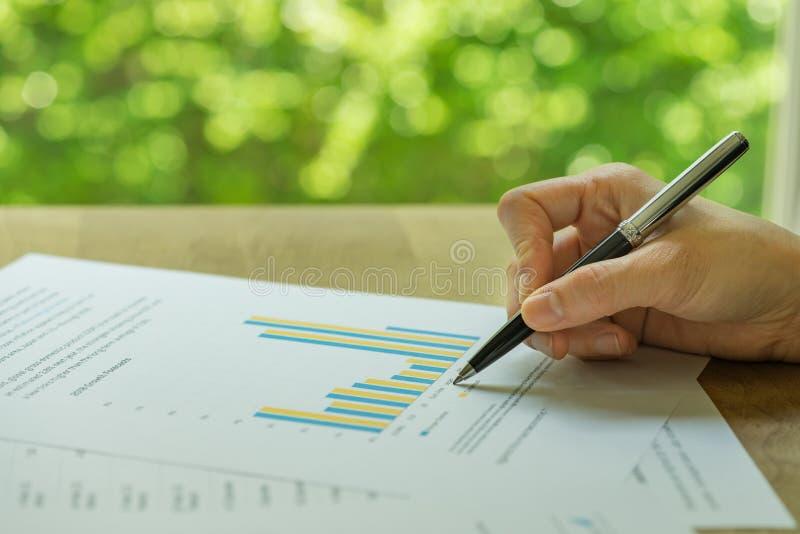事务、投资或者财政报告回顾,拿着pe的手 免版税库存照片