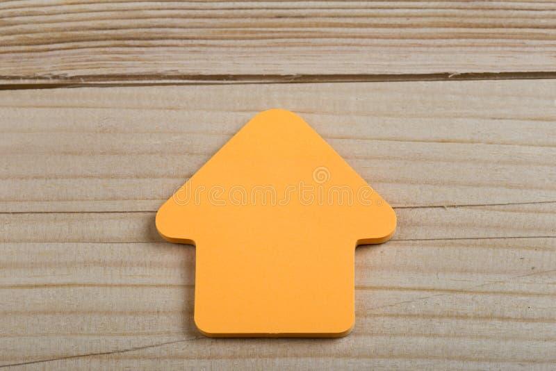 事务、未来和刺激概念-以一个箭头的形式橙色空白的贴纸在木背景 图库摄影