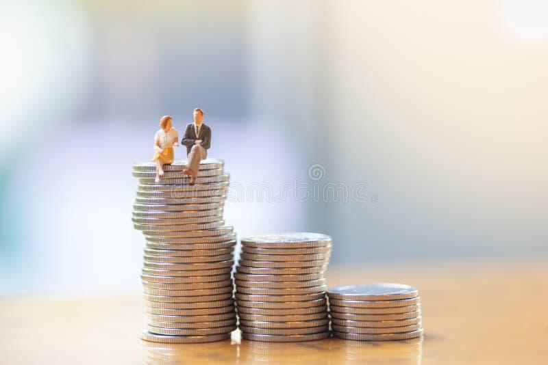 事务、财务和保存的概念 关闭商人和妇女坐和谈话在堆银币顶部 库存图片