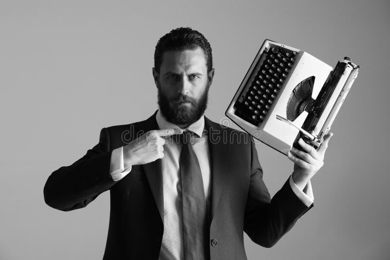 事务以老方式 蓝色衣服的与打字机的商人和领带 库存图片