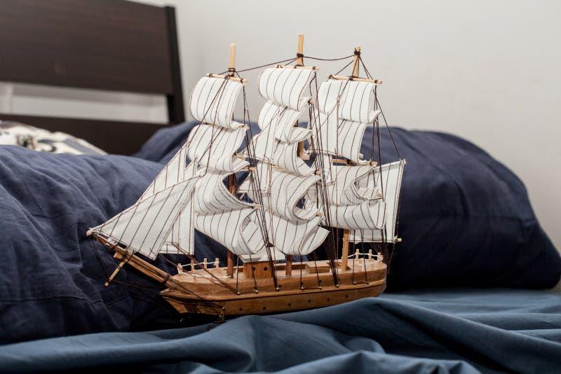 事务和创造性的概念 一艘帆船的模型在蓝色卧具的 恶梦或奇怪的梦想 免版税库存照片