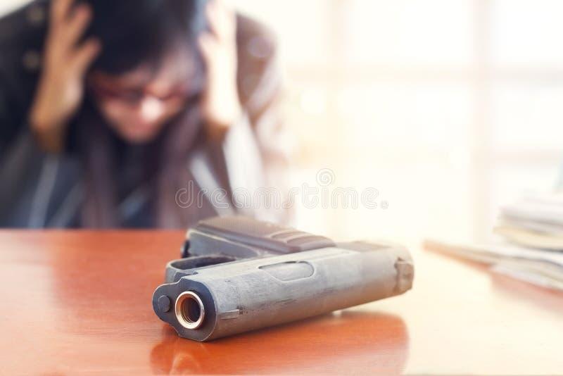 从事务和枪在桌上,选择聚焦的失败压下的商人在前面枪 图库摄影