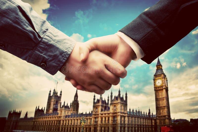 事务在伦敦。在大本钟,威斯敏斯特背景的握手 免版税图库摄影