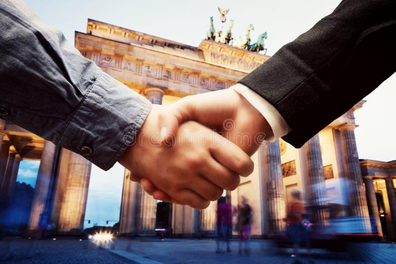 事务在柏林。在勃兰登堡门背景的握手。 免版税库存照片