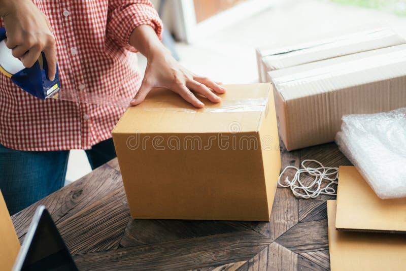 事务开始SME概念 年轻起始的工作企业家的小企业主在家,包装和交付情况 库存照片
