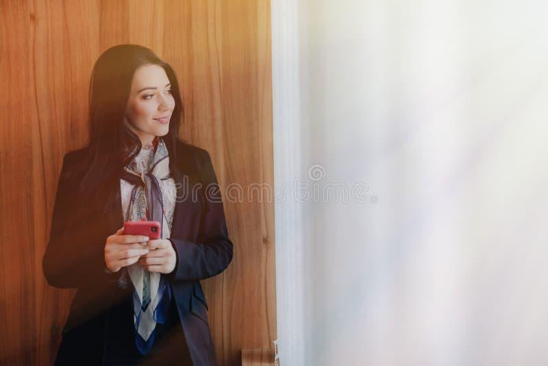 事务式衣裳的年轻情感可爱的女孩在与一个电话的一个窗口在现代办公室或观众席 库存照片