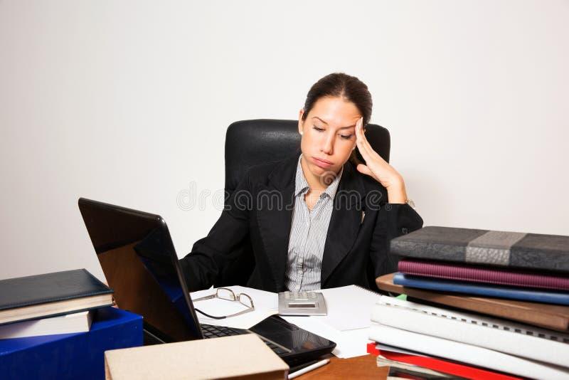 年轻事务打扮了工作在她的书桌的妇女 免版税图库摄影