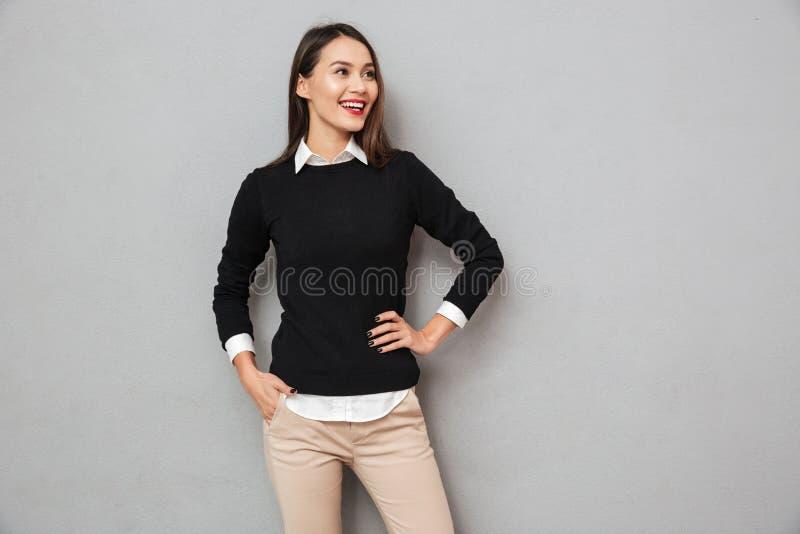 事务的愉快的亚裔妇女穿衣与在臀部的胳膊 免版税库存照片
