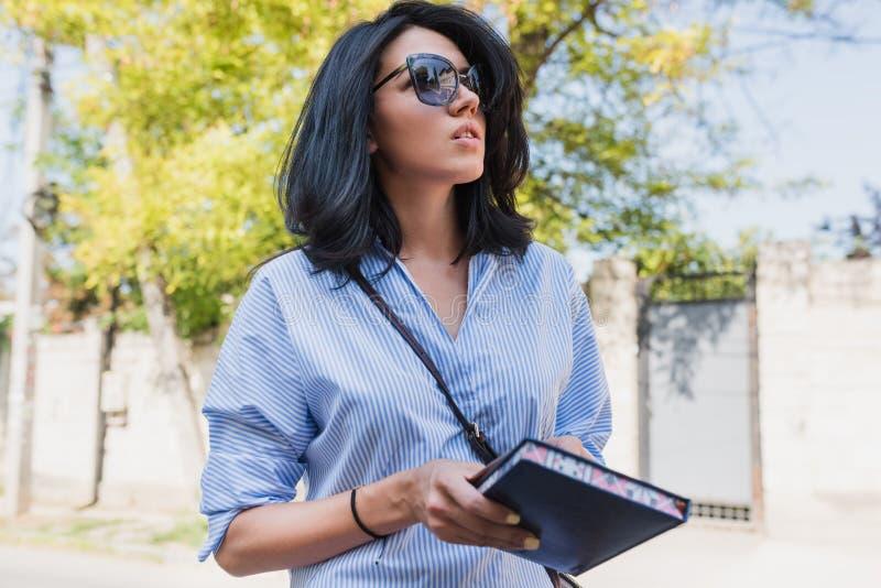 事务,人们,生活方式概念 快乐的深色的使用笔记本的企业女性经理对计划新的时期 免版税图库摄影