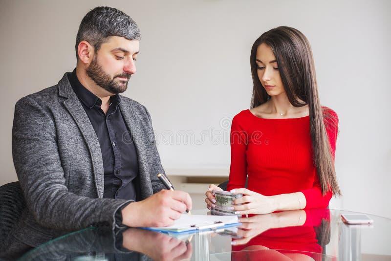 事务 女商人给人捐钱 在红色礼服打扮的妇女给贿款 灰色夹克的商人得到 库存照片