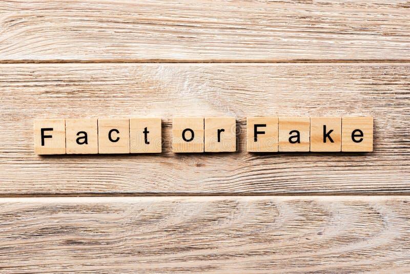 事实或在木刻写的伪造品词 事实或伪造品文本在桌上,概念 库存图片