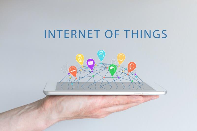 事(IOT)概念互联网用拿着巧妙的电话的手 被连接的设备喜欢巧妙的电话,巧妙的手表 图库摄影