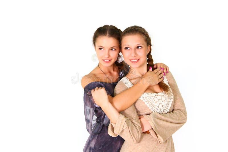 二个在空白backgroun查出的微笑的女孩女朋友拥抱 免版税库存图片