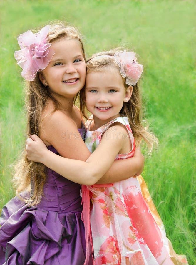 二个拥抱的逗人喜爱的小女孩纵向  免版税库存照片