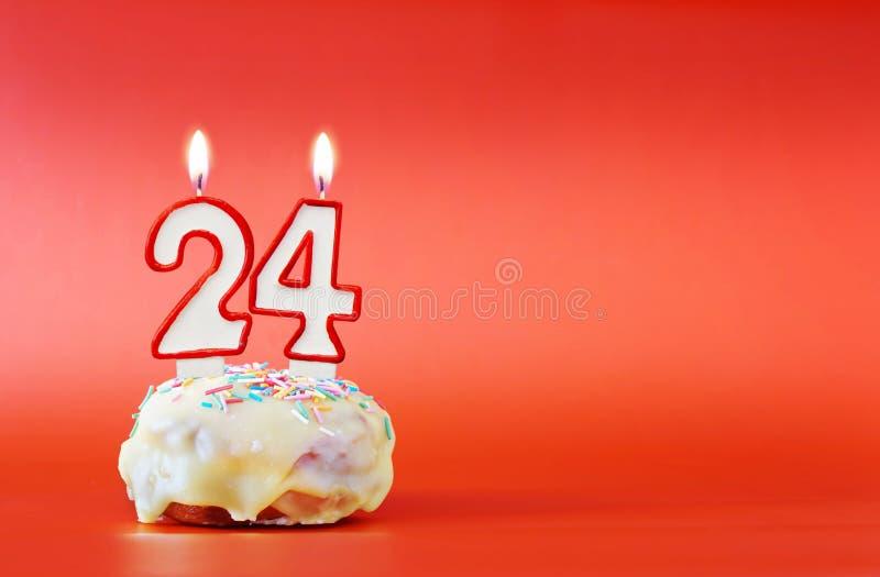二十四年生日 与白色灼烧的蜡烛的杯形蛋糕以第24的形式 图库摄影